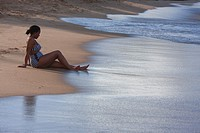 Quiet beach scene of one ethnic woman with soft ocean waves.
