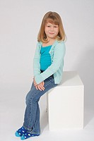 Child portrait of a blond haired girl on a white sweep wearing a green a green cami set in jean sitting on a white wood block.