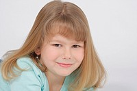 Child portrait of a blond haired girl with bangs in green shirt cropped horizontally.