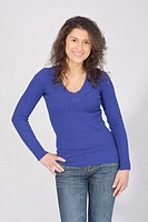 Portrait of a women in a blue long sleeve v-neck sweater in jeans on a white backdrop.