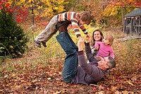 Nuclear family with parents in their 30s and with a 3 year old boy and a one year old girl playing on leaf covered lawn in fall, with a garden shed in...