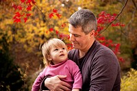Father, in his 30s, holding his one year old daughter and holding her gaze with a loving look while sitting in their backyard in the fall with red map...