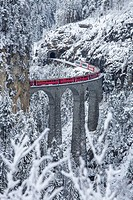 Bernina Express train passes on Landwasser Viadukt Filisur Canton of Graubünden Switzerland Europe.