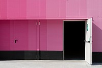 Pink industrial storage building with open door.