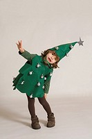 Christmas; 3 years old little girl dressed up as a Christmas tree,.