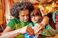 Mother and daughter (4-5) sitting at table in restaurant and sharing chocolate bar