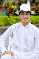 Young hispanic man in formal clothes, wearing white shirt, pants and hat, smiling at camera.