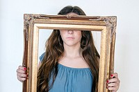 Young teen with long brown hair, with a gilded frame in hands covering her eyes.