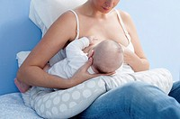Young mother feeding breast. She is using a nursing pillow with the baby on side.