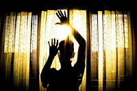 Silhouette of a person behind a curtain with open hands.