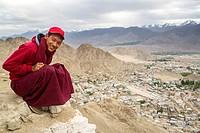 Monk guarding the Namgyal Tsemo gompa entrance, Leh (Ladakh, India). At the back, the mud-brick city of Leh and the snowy montain range.
