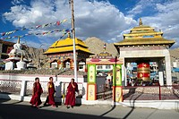 Three monks walk by a buddhist praying enclosure.