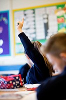 Secondary education Wales UK: a girl pupil holding her hand in the air to answer a question in a classroom lesson.