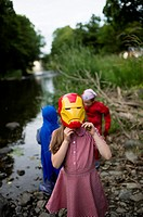 Childhood Games - young girl wearing an IronMan mask : Pre-teen primary school age children playing outdoors on a summer evening, dressed up as comic ...