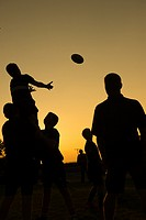 Silhouettes of young teenage men boys taking part in rugby training coaching practicing lineout ball handling, at dusk, Aberaeron Wales UK.