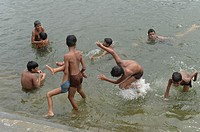 Young indian boys bathing in the waters of lake Pichola, Udaipur, India.