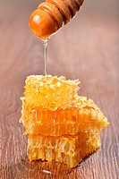 Honey dripping on honeycombs on wooden background.