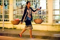 Asia. South-East Asia. Laos. Province of Luang Prabang, city of Luang Prabang, World heritage of UNESCO since 1995. Woman carrying baskets.