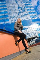 Tee girl posing before shiny-glass skyscraper house