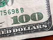 Closeup of the number 100 in the corner of a $100 bill