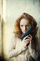 Redhead woman holding a gun.