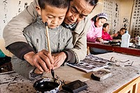 Teacher and pupil at traditional calligraphy school. Lijiang, China.