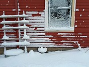 Snow collecting on the side of a red house after a winter storm.