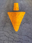 Yellow arrow painted on asphalt with a tire track running through it.