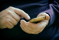 Male hands entering information on smart phone.