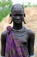 Mursi girl without lip plate but with ear disks. Mursi or Mun people are pastoralist and reside in Debub Omo Zone in the border of South Sudan. Omo Na...