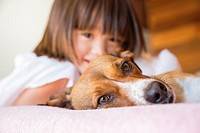 Toddler girl and her pet dog laying on the bed.