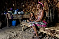 Mbororo woman with her child inside her hut .