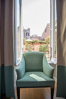 Chair in a window with cityscape behind in Rome, Italy.