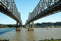 A tug boat pushes a barge beneath the bridge over the Mississippi at Natchez, TN. Tub.