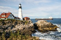 View of the landmark Portland head lighthouse in Maine as a ocean freighter approaches.