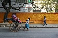 India, 19 February 2016. Hand pulling rickshaw puller pulling with passenger walks past a colorful wall at street of Kolkata.