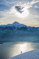 Hiker admires Lake Como and Mount Legnone on a cold winter morning Vercana mountains High Lario Lombardy Italy Europe.