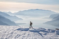 Winter view of Lake Como while a hiker proceeds with snowshoes Vercana mountains High Lario Lombardy Italy Europe.