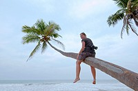 Young woman with the camera sitting on a palm tree, Hikkaduwa, Sri Lanka, South Asia.