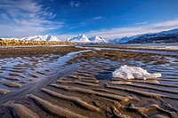 The icy sandy beach surrounding the snow capped mountains Breivikeidet Lyngen Alps Tromsø Lapland Norway Europe.