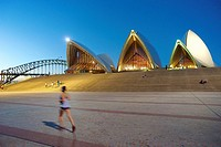 jogger and Sydney Opera House at dusk, with Harbour Bridge in the background.