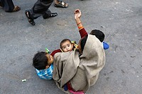 India 13 February 2016. A woman with three children begs alms to people walking past on near the Tomb of Sufi Saint Khwaja Chishti in Ajmer.