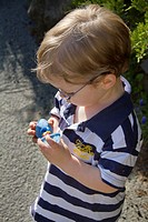A young boy inspecting his Easter candy after a hunt.