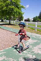 A young boy rides a scooter outdoors in Post Falls, Idaho, USA.