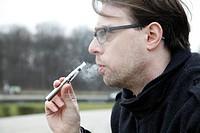 Young man smoking an e-cigarette