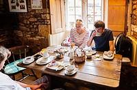 A family enjoy a cream tea at the Plough Inn , . Ford , . Temple Guiting , . Cheltenham , England , Britain , Uk.