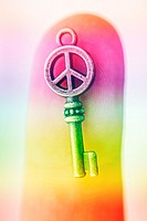 Close-up of small metal key with peace sign on person´s finger. Multicolor toned. From above. Unrecognizable.