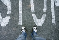 Male feet standing on asphalt with stop sign marking.