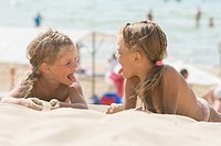 Two happy little girls show each other tongues on a sandy beach.
