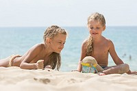 Two little girls are playing with enthusiasm in the sand on the seashore.